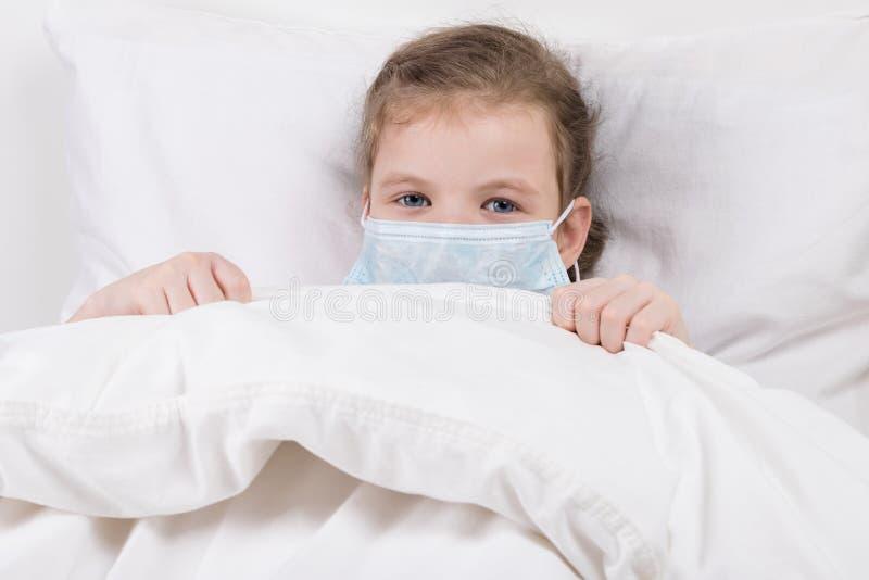 Dziewczynka kłama bolączkę w białym łóżku z bandażem na jej twarzy zdjęcia royalty free