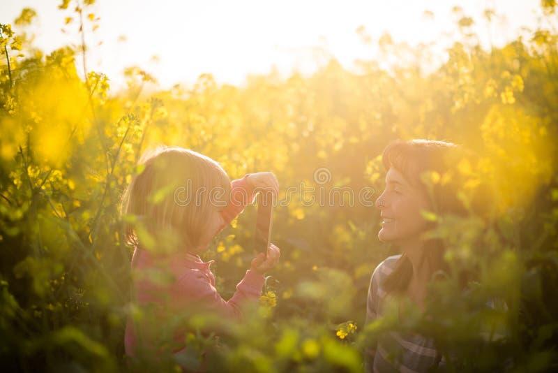 Dziewczynka klika obrazek jej matka outdoors zdjęcie stock