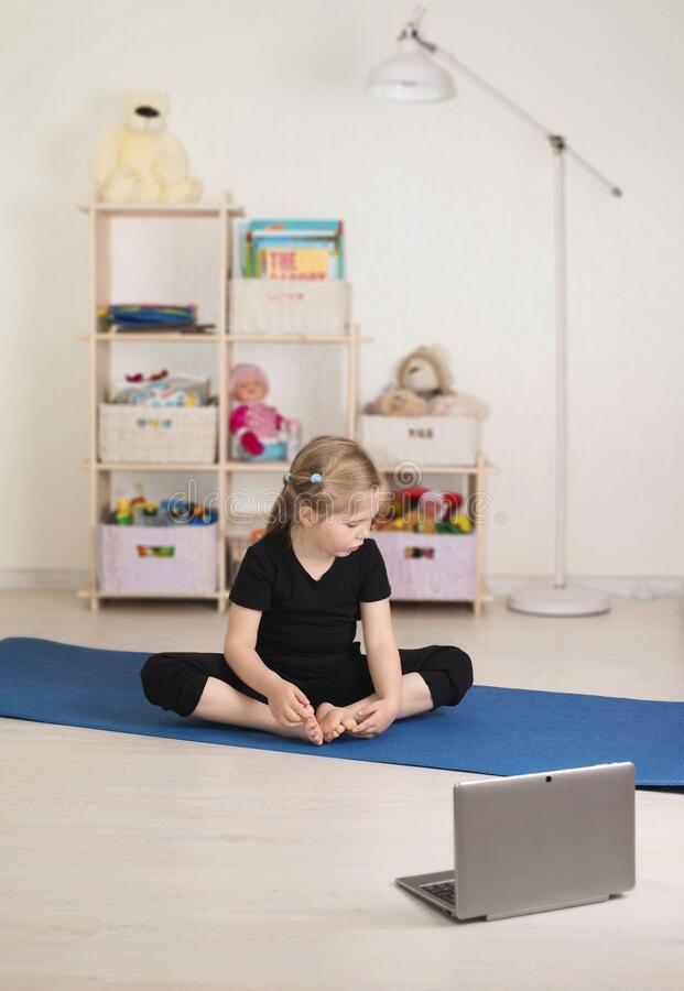 Dziewczynka oglądająca filmy online na laptopie i ćwicząca w swoim pokoju w domu Odległe obraz royalty free