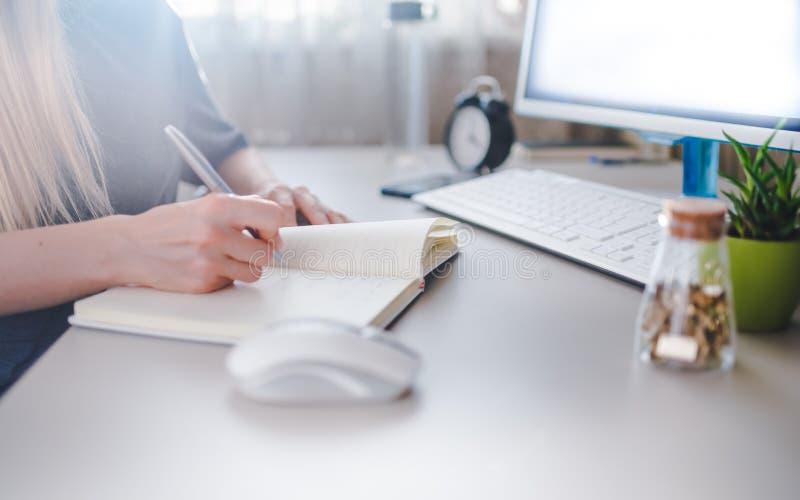 Dziewczynka pisze w notatniku, sporządza harmonogram na tydzień fotografia stock