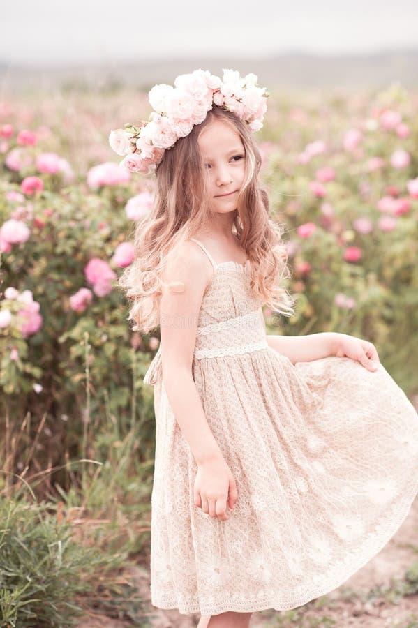 Dziewczynka pozuje w ogródzie różanym obraz stock
