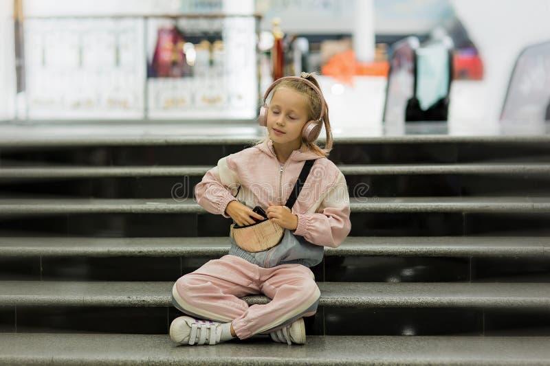 Dziewczynka słucha muzyki w pomieszczeniach dzięki nowoczesnym słuchawkom Dziewczynka słucha słuchawek Lista odtwarzania konta mu fotografia royalty free