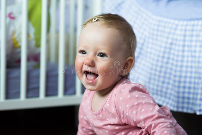 Dziewczynka siedzi na podłoga w menchii sukni w domu, ono uśmiecha się obraz stock