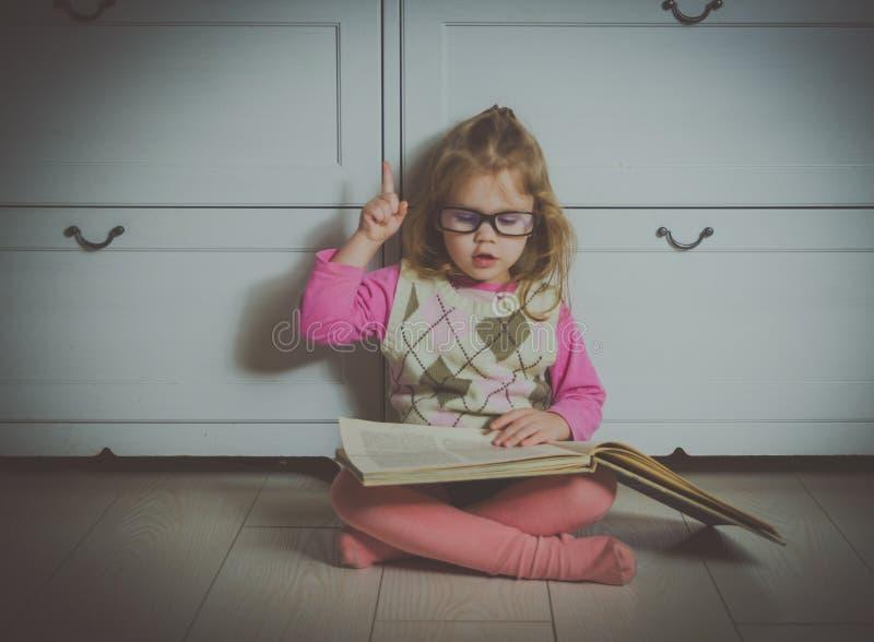 Dziewczynka siedzi na podłoga z książką i szkłami fotografia stock