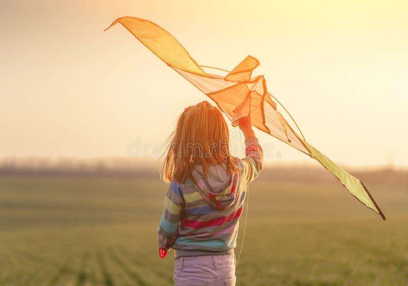 Dziewczynka trzymająca latawiec o zachodzie słońca zdjęcia royalty free