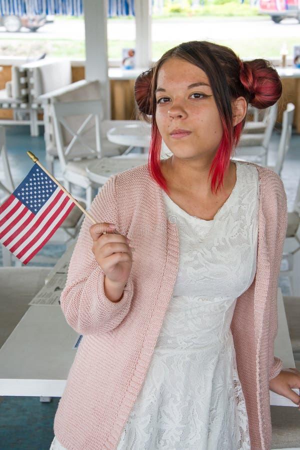 Dziewczynka uśmiecha się i trzyma amerykańską flagę, święta narodowe, plan średni obraz stock