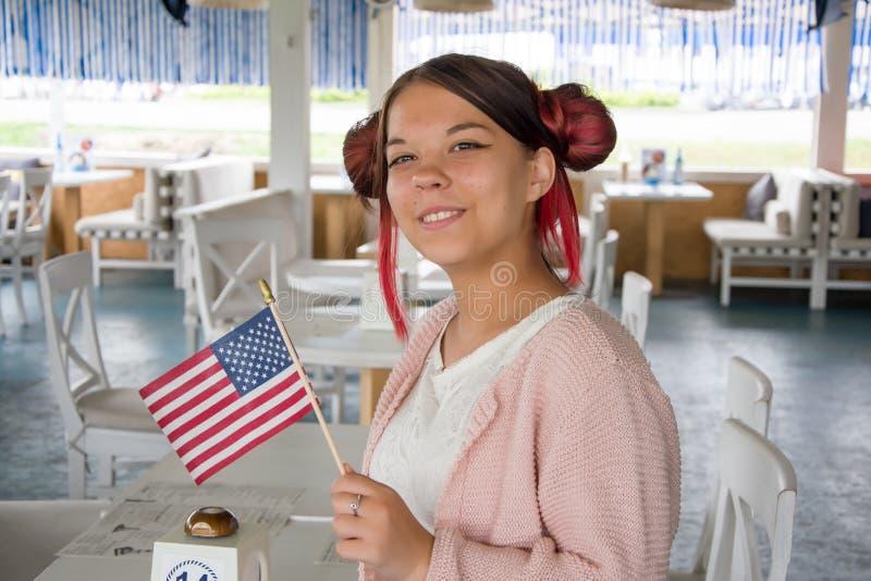 """Dziewczynka uÅ›miecha siÄ™ i trzyma amerykaÅ""""skÄ… flagÄ™, Å›wiÄ™ta narodowe, plan Å›redni zdjęcie stock"""