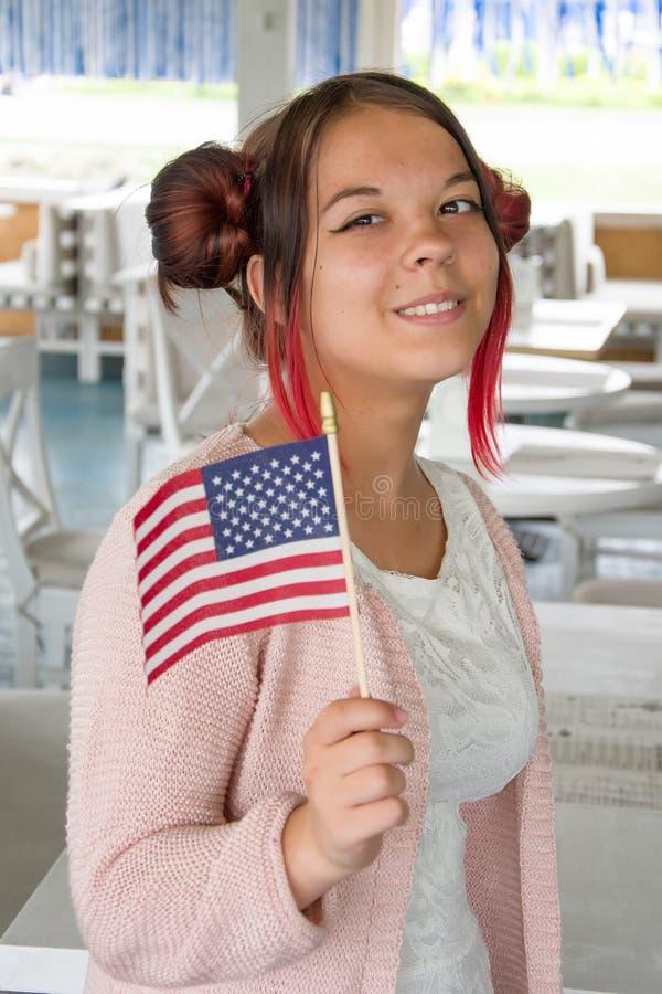 "Dziewczynka uÅ›miecha siÄ™ i trzyma amerykaÅ""skÄ… flagÄ™, Å›wiÄ™ta narodowe, plan Å›redni zdjęcia stock"