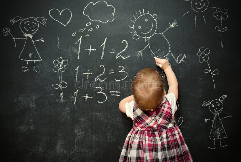 Dziewczynka uczeń rysuje kredę na blackboard fotografia royalty free