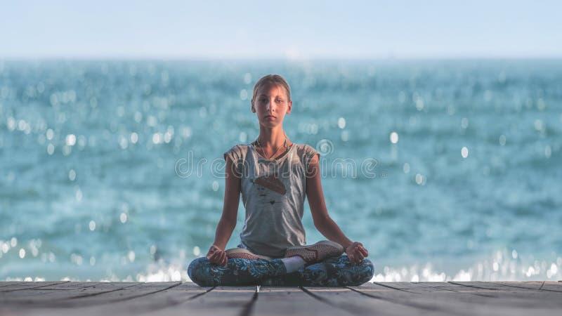 Dziewczynka w Lotosowej pozie na tle morze zdjęcia stock