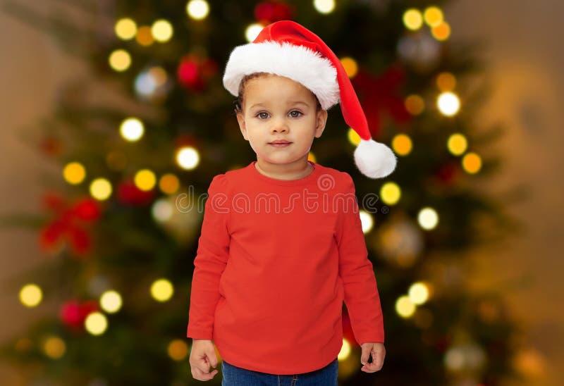 Dziewczynka w Santa kapeluszu nad choinek światłami fotografia stock