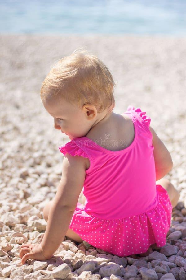 Dziewczynka w swimsuit obsiadaniu na plaży morzem fotografia stock