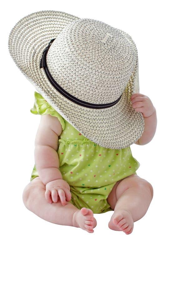 Dziewczynka w zieleni sukni bawić się peekaboo z dużym słomianym kapeluszem fotografia stock