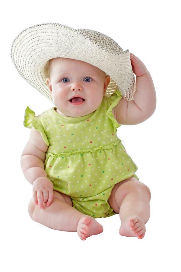 Dziewczynka w zieleni sukni siedzi będący ubranym dużego słomianego kapelusz zdjęcia stock