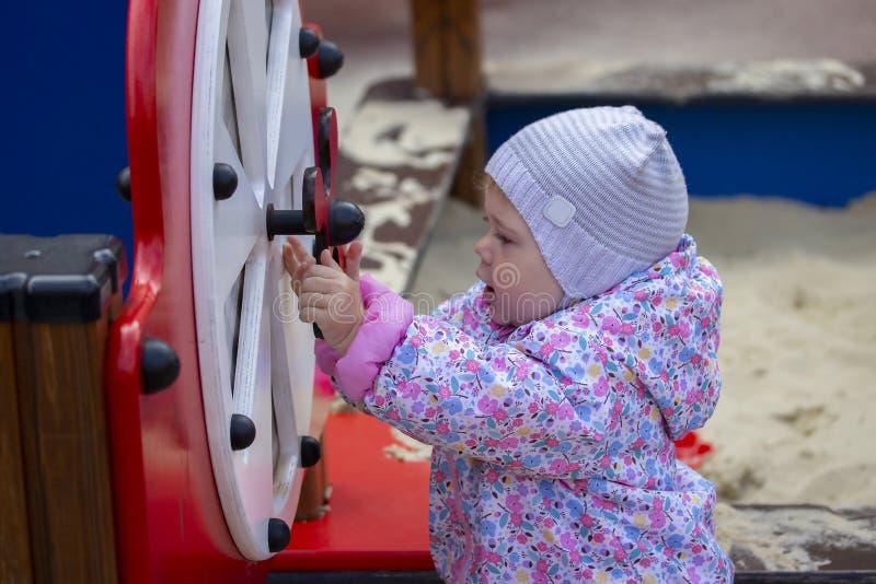 Dziewczynka wiruje zabawkarskiego toczy wewnątrz boisko Dziewczyn sztuki w jardzie Dzieciak bada jego jarda w szarym kapeluszu ch fotografia stock