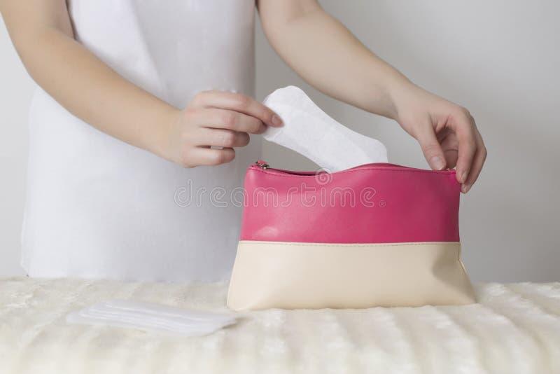 Dziewczynka wkłada do torebki podpaskę sanitarną na wypadek menstruacji, sucha i higieniczna koncepcja, kobiecość obrazy stock