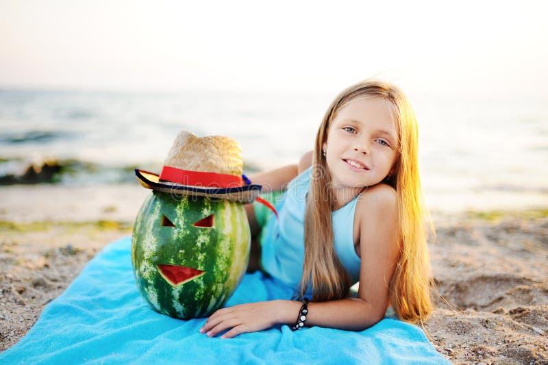 Dziewczynka z arbuza lying on the beach na plaży przeciw morzu zdjęcie royalty free
