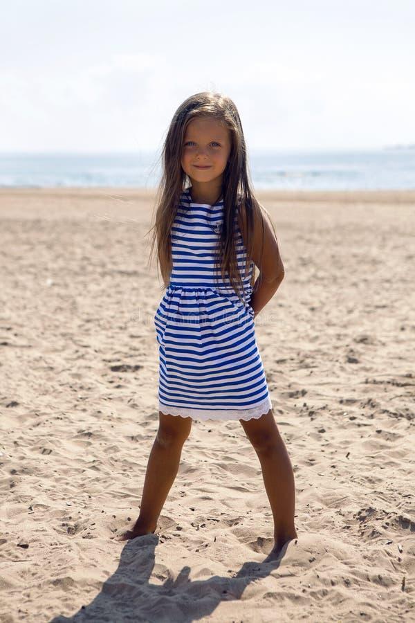 Dziewczynka z długie włosy w pasiastej błękit sukni fotografia stock