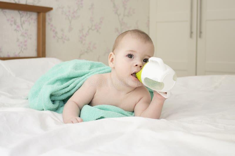 Dziewczynki chłopiec zawijająca w ręczniku, woda pitna od filiżanki, miękka ostrość zdjęcie royalty free