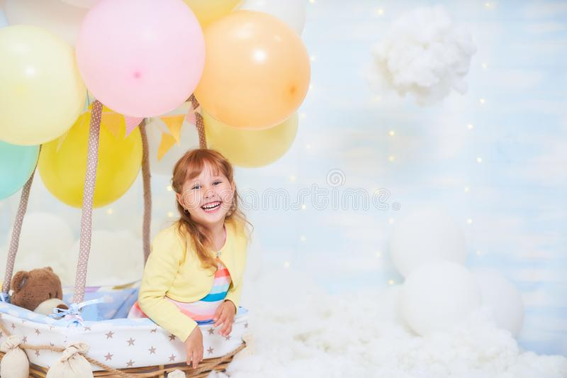 Dziewczynki obsiadanie na chmurze obok kosza podróżuje i lata z balon w chmurach, lotników szkłami i kapeluszem fotografia stock