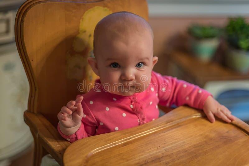 Dziewczynki obsiadanie w highchair przyglądającym przy mamą up obrazy royalty free