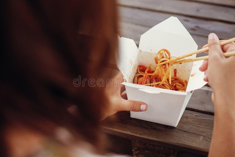 Dziewczyny łasowania wok kluski z warzywami i owoce morza w kartonie boksują iść, z bambusowymi chopsticks, zbliżenie Tradycyjny  zdjęcie stock
