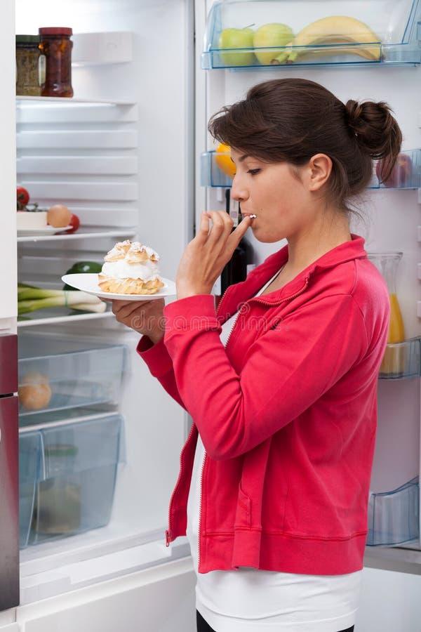 Dziewczyny łasowania śmietanki tort zdjęcie royalty free