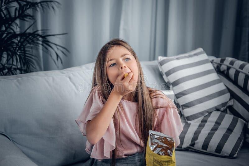 Dziewczyny łasowania cukierki siedzi na kanapie obraz royalty free