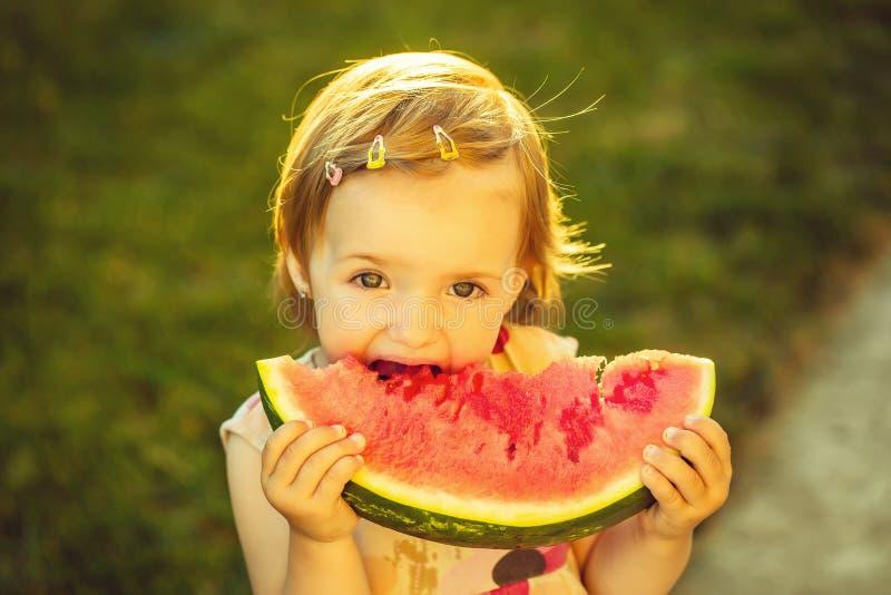Dziewczyny łasowania czerwony arbuz plenerowy zdjęcie stock