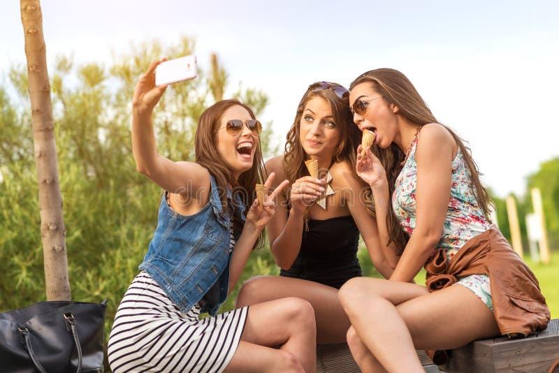 3 dziewczyny łasowania piękny lody podczas gdy Selfie fotografia zdjęcia stock