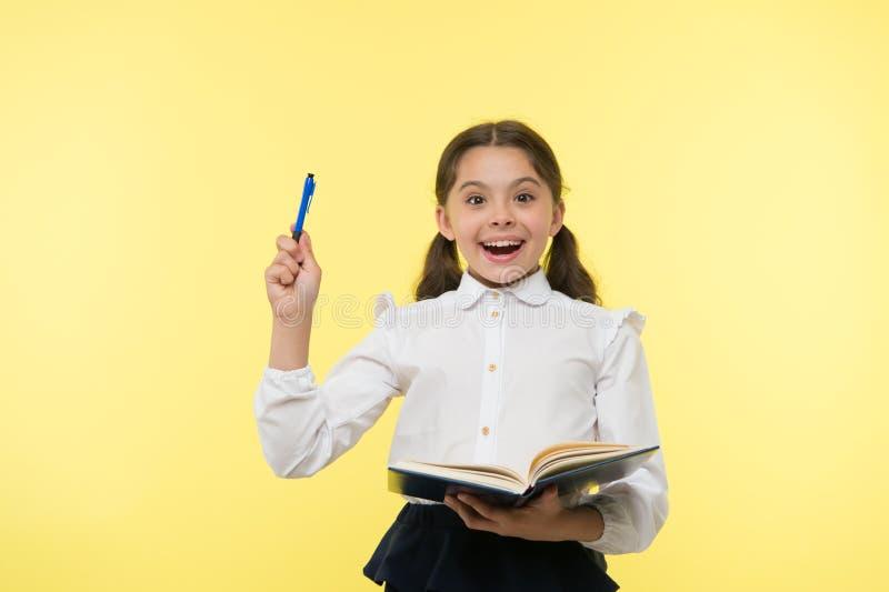 Dziewczyny śliczna uczennica w jednolitym chwyta podręcznika lub książki koloru żółtego tle Skrzętny uczeń dostaje wiedzę od ksią zdjęcia stock