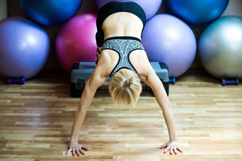 Dziewczyny atleta robi handstand z nogami na stepper w gym fotografia royalty free