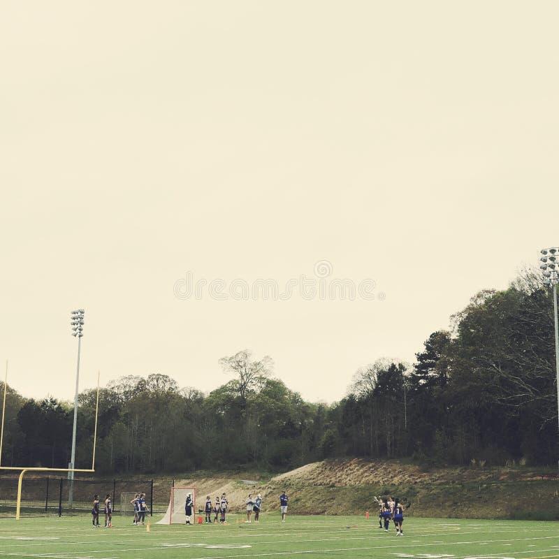 Dziewczyny bawić się lacrosse na polu obraz stock