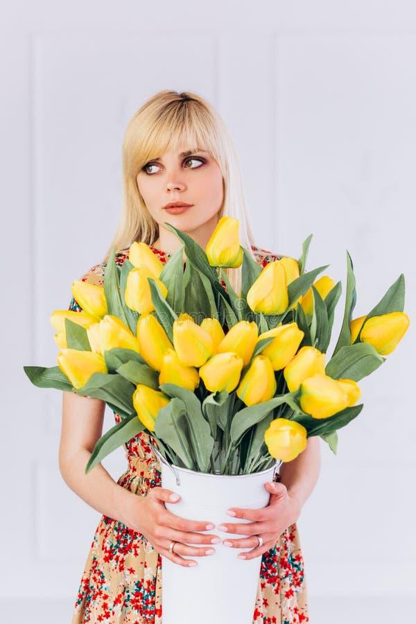 Dziewczyny blondynka z bukietem żółci tulipany w jej rękach spotyka wiosnę obraz royalty free