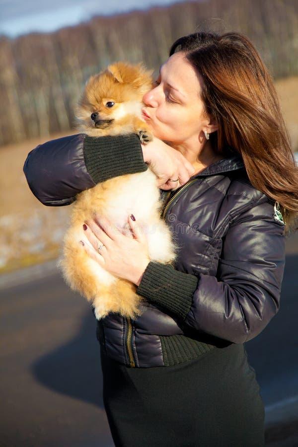 Dziewczyny całowania szczeniaka spitz pies z miłością. zdjęcia stock