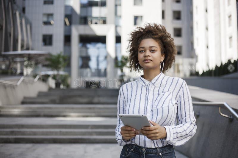 Dziewczyny ciemnoskórzy stojaki na ulicie blisko spojrzeń i budynku biurowego prosto Trzyma pastylkę obraz royalty free