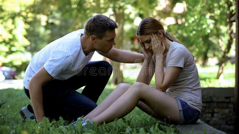 Dziewczyny cierpienie od migreny, siedzi w parku, mężczyzna dzwoni karetkę, pierwsza pomoc obrazy stock