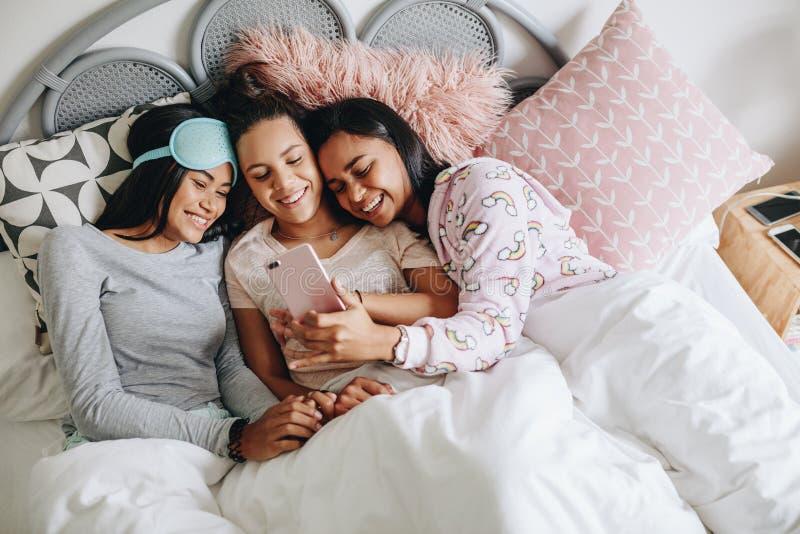 Dziewczyny cieszy się z telefonem komórkowym podczas sleepover obraz stock
