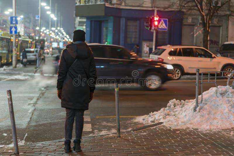 Dziewczyny czekanie krzyżować drogę podczas gdy zwyczajni światła ruchu są czerwoni w nocy mieście obrazy royalty free