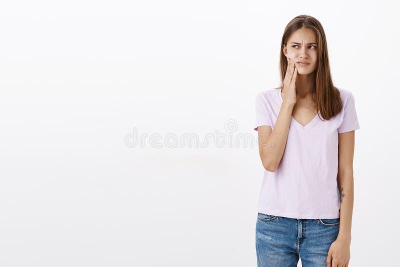 Dziewczyny czuciowa niewygoda w usta ma rozpadową pozycję przeszkadzającą i nieradą po sączyć zimnego napój patrzeje z lewej stro zdjęcie royalty free