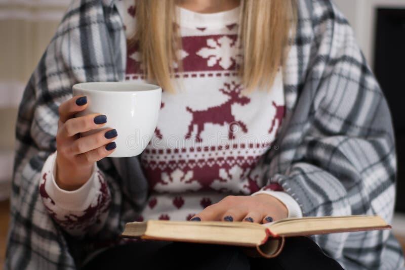 Dziewczyny czytelnicza książka i pić gorącej herbaty w długiej zimy nocy w domu zdjęcia royalty free