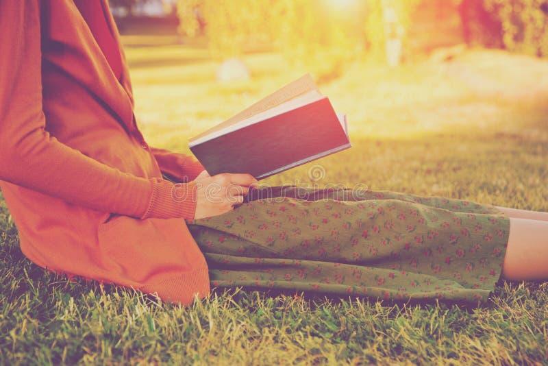 Dziewczyny czytelnicza książka przy parkiem zdjęcia stock