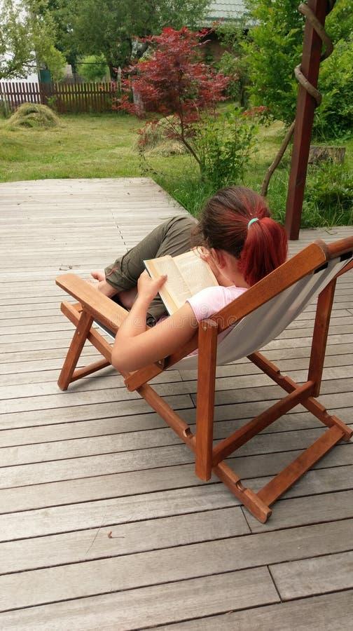 Dziewczyny czytelnicza książka w pokładu krześle obrazy royalty free