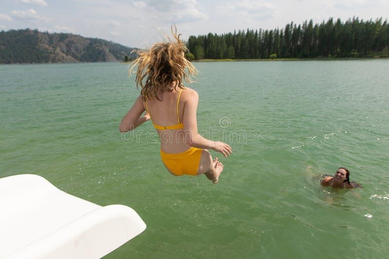 Dziewczyny doskakiwanie w jezioro od wodnego obruszenia fotografia stock