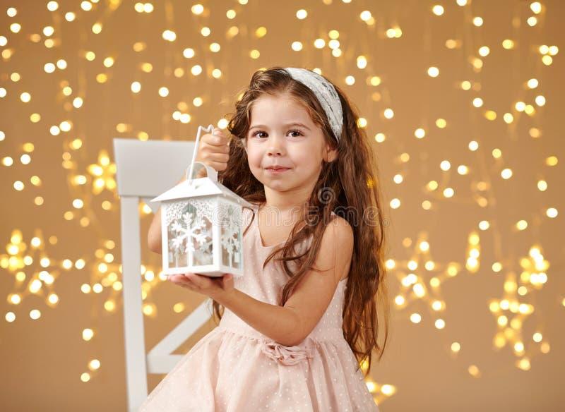 Dziewczyny dziecko pozuje z lampionem w bożonarodzeniowych światłach, żółty tło, menchia ubiera zdjęcie stock