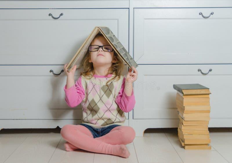 Dziewczyny dziecko siedzi na podłoga z książką z szkłami obrazy stock