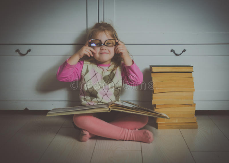Dziewczyny dziecko siedzi na podłoga z książką z szkłami, fotografia stock