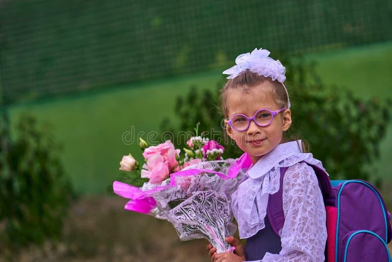 Dziewczyny dziecko w mundurku szkolnym z łękami, szkłami i szkolną torbą na jego tylnym, iść pierwsza klasa szkoła na Wrześniu obrazy stock