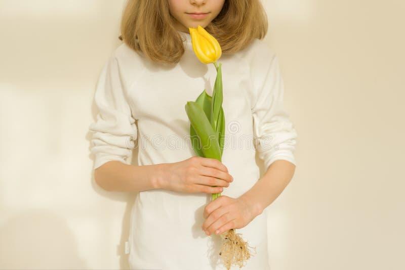 Dziewczyny dziecko z żółtym tulipanowym kwiatem, pogodny jaskrawy ścienny tło, w górę obraz stock