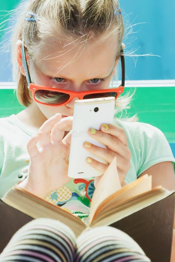 Dziewczyny dziecko z telefonem i książką fotografia stock